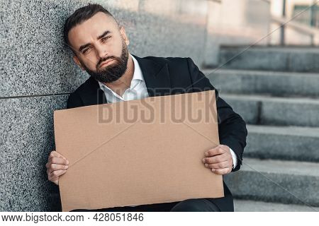 Unemployment Growth Concept. Despaired Businessman Holding Empty Cardboard Sign, Sitting Outdoors, C