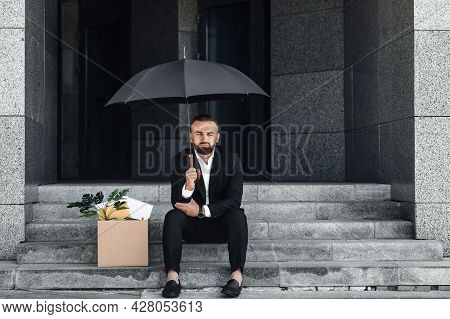 Unemployment Concept. Jobless Mature Businessman Sitting Under Umbrella With Empty Poster And Box Of