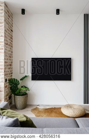 View Of Black Blank Tv Screen Seen From Comfy Grey Couch In Stylish Minimalist Living Room With Bric