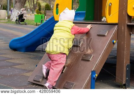 Little Girl Is Played In The Playground. Child In Warm Clothes Walks In The Playground