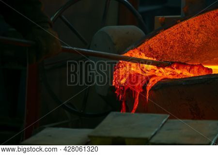 Red Molten Metal Is Pulled Out Of The Vat At The Production Site. Metallurgy Of Casting Products