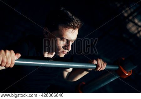 Young Handsome Man Performs Pull-ups On Horisontal Bar To Strengthen Muscles Outdoors In The Morning