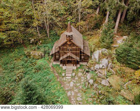 Wooden Pilgrimage Rural Chapel Of Virgin Mary, Cz: Stozecka Kaple And Iron Cross Standing In Forest