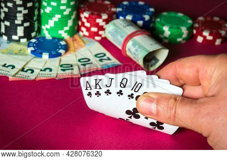 Poker Cards With Royal Flush Combination. Close Up Of Gambler Hand Takes Playing Cards In Casino.