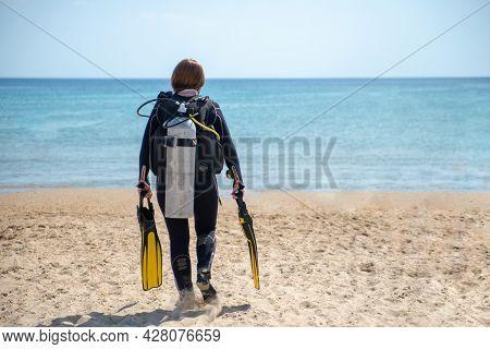 Scuba Diver. Diver Girl Walks Along The Beach Towards The Sea