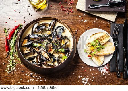 Blue mussels in cream wine sauce. Delicious healthy Italian traditional food closeup served for lunch in modern gourmet cuisine restaurant.