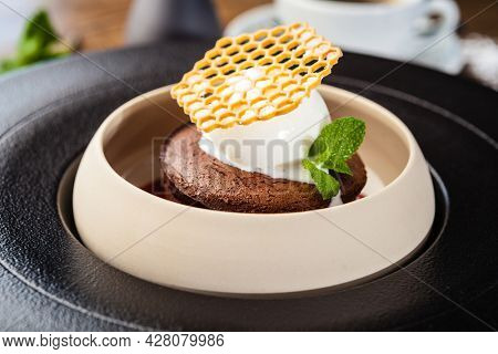 Chocolate fondant. Dark chocolate, raspberry sauce, vanilla ice cream dessert. Delicious healthy traditional food closeup served for lunch in modern gourmet cuisine restaurant.
