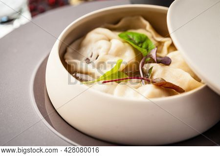 Black Angus beef hand-made dumplings. Cucumber-julienne with chilli-garlic butter and sour cream. Delicious healthy traditional food closeup served for lunch in modern gourmet cuisine restaurant.