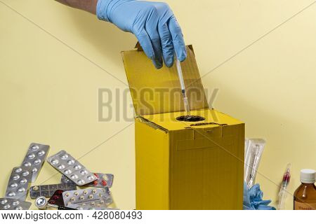 Yellow Disposal Box For Contaminated Or Infectious Products In A Hospital Or Home. Hand Putting A Sy