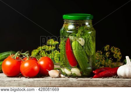 Pickled Cucumbers In Glass Jars And Spices And Vegetables For Preparation Of Pickles On Black Backgr