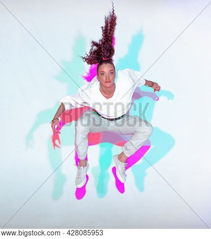 Jumping Stylish Mixed Race Young Girl On White Background. Rainbow Colourful Studio Light. Fiery Hip