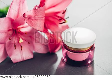 Jar With Moisturizer Cream Surrounded With Pink Lily Flowers On Grey Background. Organic Cosmetics.