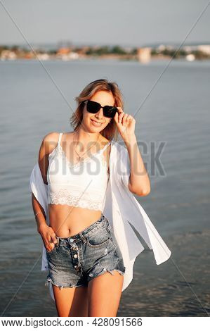 Photo Of A Woman In Sunglasses. Portrait Of A Beautiful Young Woman In Short Denim Shorts, A White T