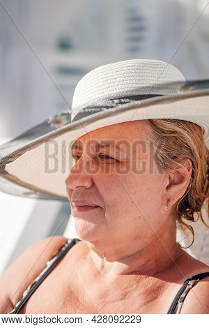 A Woman In A Straw Hat. Profile Portrait Of A Charming Woman In A White Straw Hat Relaxing On The Be