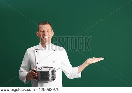 Happy Male Chef With Cooking Pot On Dark Green Background. Space For Text