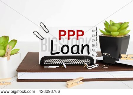 Paycheck Protection Program Ppp Loan. Business Card Holder On A Work Table, On A Notebook, Near A Fl