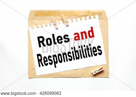 Roles And Responsibilities, Text On Paper On Craft Envelope On White Background