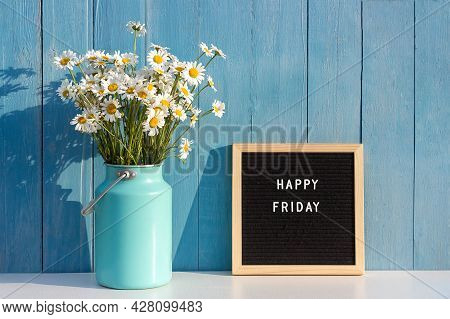 Happy Friday Words On Black Letter Board And Bouquet Of Chamomile Flowers On Table Against Blue Wood