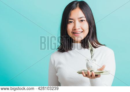 Asian Beautiful Young Woman Holding Piggy Bank On Hands And Putting Dollars Money Banknotes, Portrai