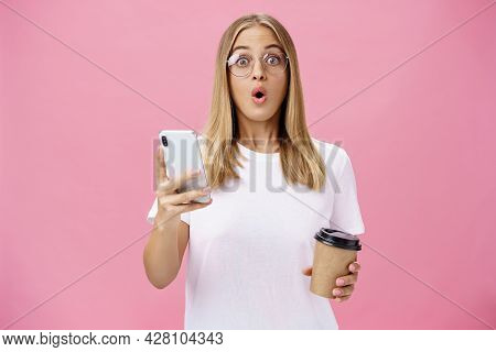 Girl Receiving Awesome Message On Smartphone While Drinking Coffee From Cup In Cafe Sharing News Wit