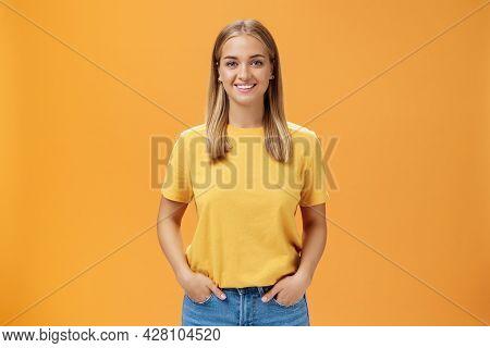 Cute Chubby Female With Tanned Skin And Fair Hair Posing Optimistic And Joyful Against Orange Backgr