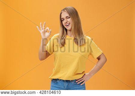 Confident And Skillful Female Student Assuring Teacher She Do Great Job Holding Hand On Waist Winkin