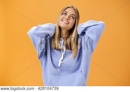 Young Pleased And Tender Woman With Tanned Skin Feeling Cozy In Warm In Trendy Hoodie Touching Back