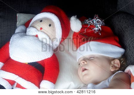 A Young Boy Sleeping With Santa