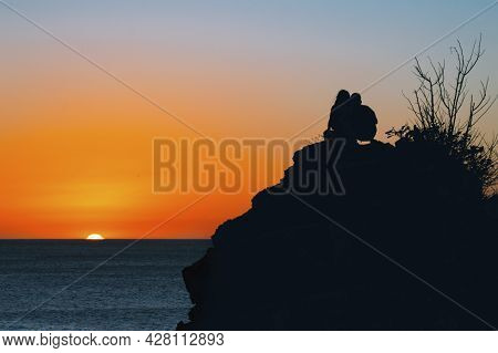 Boy And Girl On A Rock Watching The Sunset, Silhouettes Of Couple Watching The Sunset