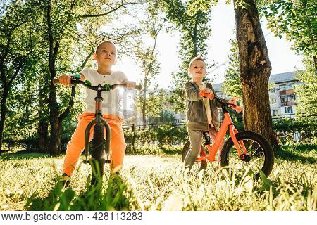 Two Boys Riding Balance Bikes In Park.