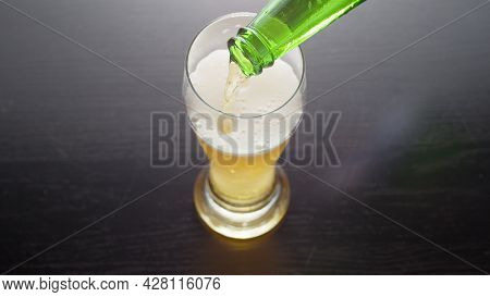 Pouring beer into glass from bottle, view from above. Half pint of frothy fresh lager beer on table. Top view.