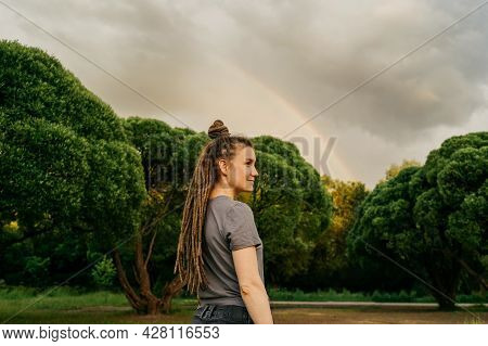 Profile View On Smiling Woman In Park.