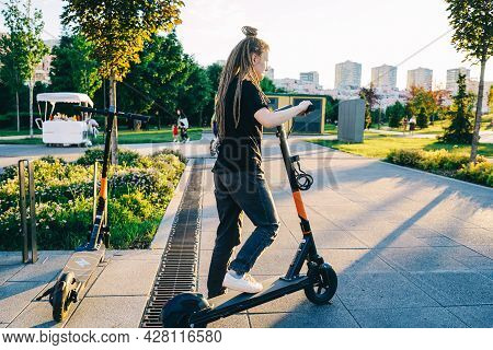 Woman Rent An Electric Scooter In Park.