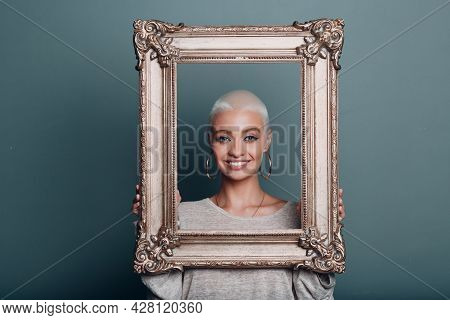 Millenial Young Woman Smiling Portrait With Short Blonde Hair Holds Gilded Picture Frame In Hands Fr