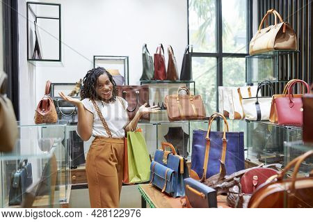 Portrait Of Happy Shopaholic Smiling At Camera While Choosing And Buying Bags For Herself In The Sho