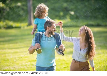 Happy Foster Family Of Mother And Father Carrying Adoptive Boy Child On Shoulders, Adoption.