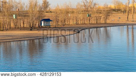 Autumn Landscape - View Of The Bay, Empty Sandy Beach With A Beach House And Trees Without Leaves Th
