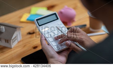 Man Calculating Financial Chart For Investment To Buying Property With House Model. Money Saving Con