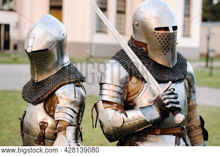 Two Knights In Armor On The Background Of A Medieval Castle.a Medieval Concept.metallic Texture