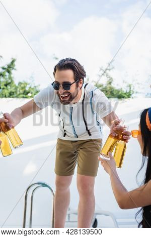Cheerful Man In Sunglasses Giving Beer To Women During Party At Poolside