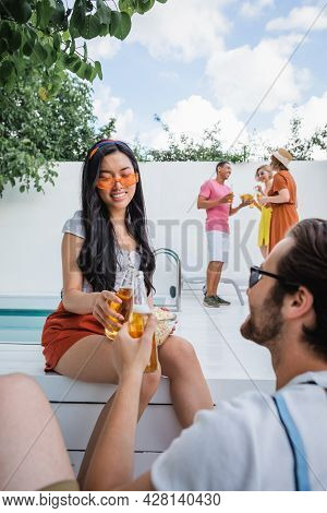 Asian Woman In Sunglasses Clinking Bottles Of Beer With Man Near Multicultural Friends On Blurred Ba