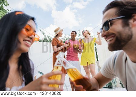 Blurred Interracial Man And Woman Clinking Bottles Of Beer Near Happy Friends