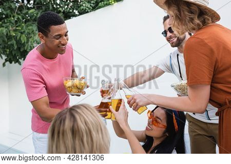 Excited Multiethnic Friends Clinking Bottles Of Beer During Summer Party