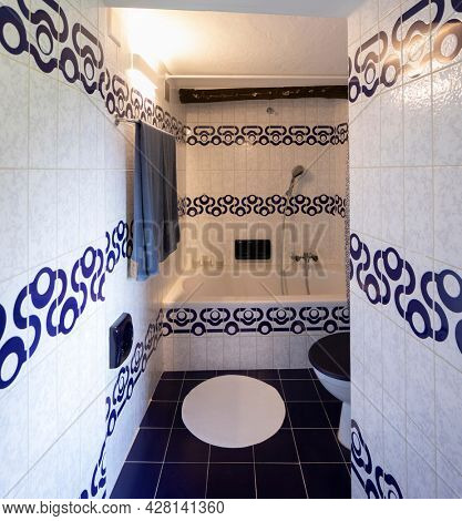 Front view bathroom with blue and white tiles. Down the hall is a bathtub with a shower. Nobody inside.
