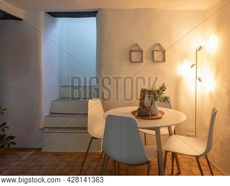 Detail of modern living room of a mountain house with a table, four designer chairs. Nobody inside