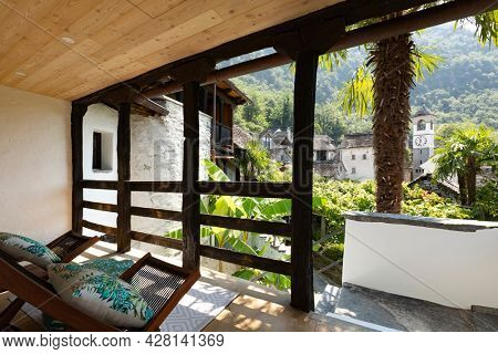 Bright patio with wooden ceiling and railing. Two comfortable rocking chairs to enjoy the Swiss mountain landscape. Nice sunny day. Nobody inside.