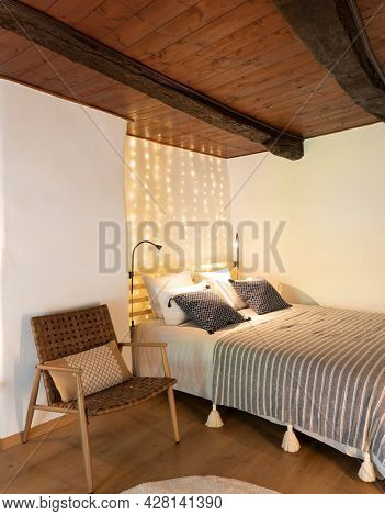 Intimate bedroom with large double bed, lots of lights above. A vintage chair makes the atmosphere more romantic. Nobody inside