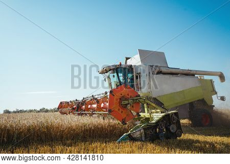 Combine Harvester Harvests Ripe Wheat. Background. Concept Of A Rich Harvest. Agriculture Image