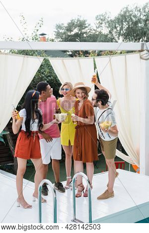 Multiethnic Friends In Summer Clothes Smiling During Party In Patio At Poolside
