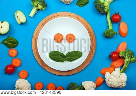 Yummy Toddler Food In White Plate On Blue Background. Concept First Complementary Food Made From Fru